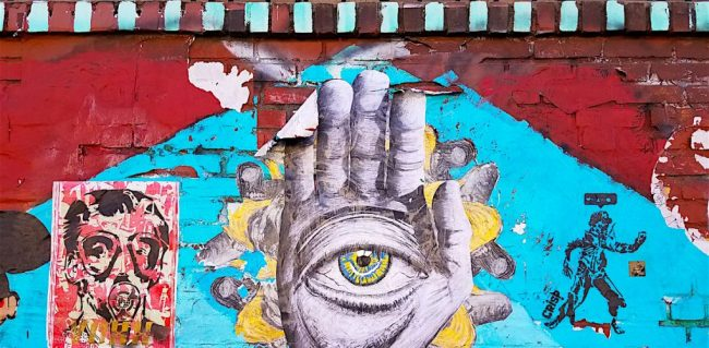 Art on a wall with an eye in the palm of a hand.